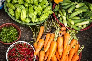Frisches Karotten, Gurken, Chilis und Essiggurken in Schalen und auf dem Tisch.
